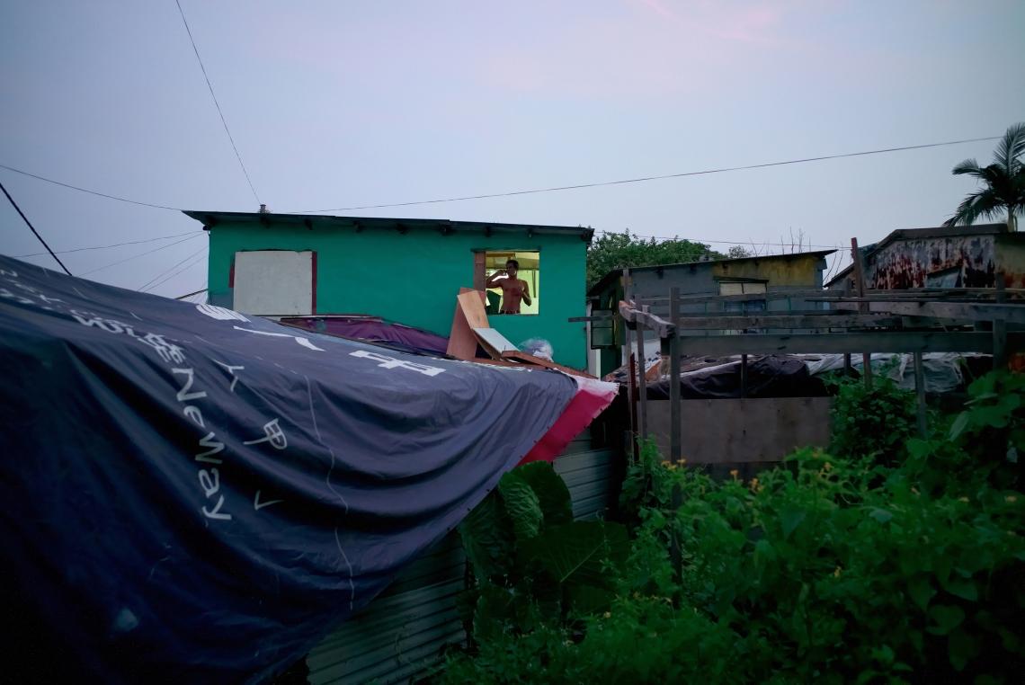 Ramesh 是斯里蘭卡人,三十五歲,來港八年。他正在藍地的自行搭建的小屋內,靠著窗邊談電話。大約四十人住在此地。香港,2015年7月。