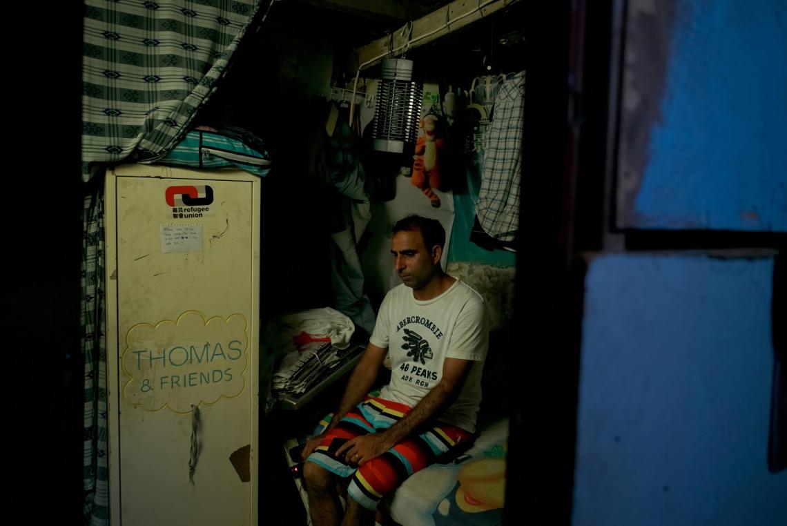 Paula 是一名三十七歲的難民,來自巴基斯坦,來港七年。他坐在床上,藍地狹小的房子裡沒有窗戶也沒有冷氣。香港,2015年7月。