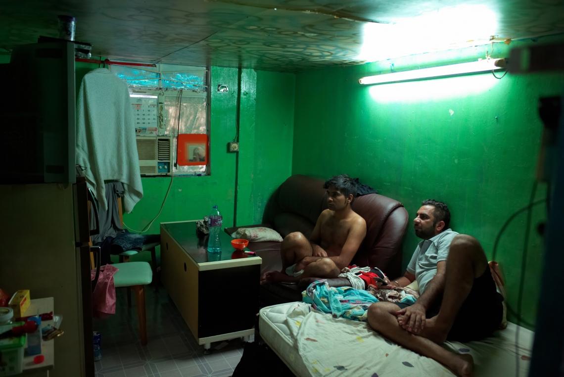 兩名印度難民正在他們泥圍破落的房子裡看電視,此房子前身為豬舍。香港,2015年8月。