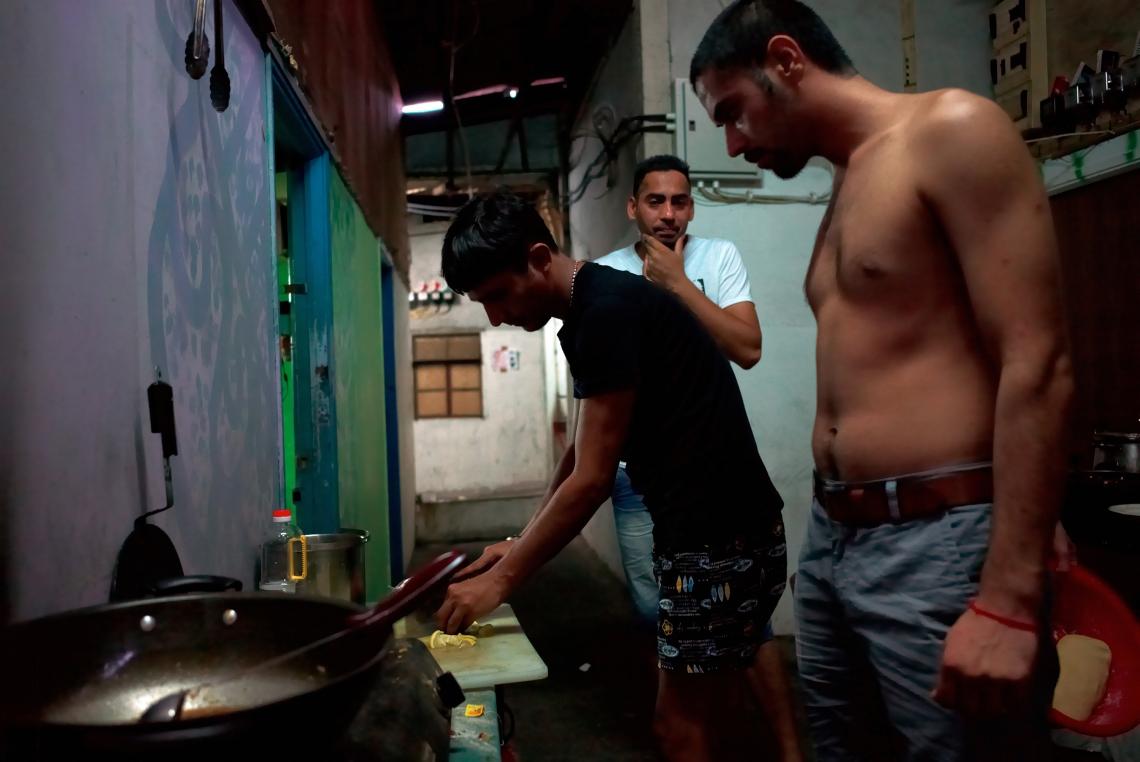 三名年青的印度難民正在泥圍的破落房子裡準備晚飯。難民之間互相團結。香港,2015年8月。