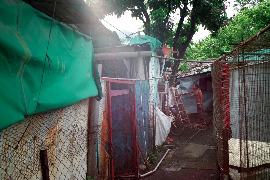 Hosen 是來自孟加拉的二十七歲難民,來港六年。他在修理他在鍾屋村破落房子的屋頂。香港,2015年7月。