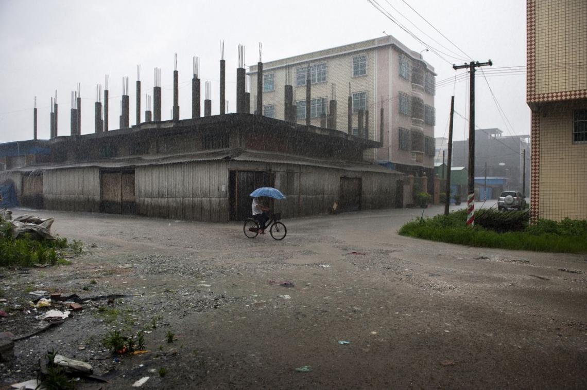 中國貴嶼鎮,2013年五月,一個男子在雨中踏單車。