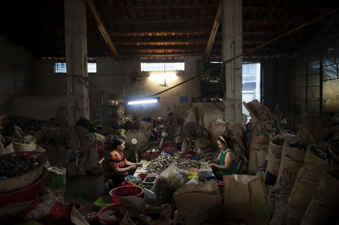 中國貴嶼鎮,2013年五月,兩個女子在非法工場中,將電子晶片按物料、顏色和大小分類。