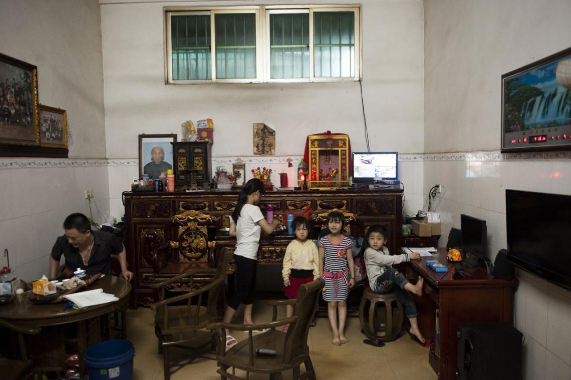 中國貴嶼鎮,2013年五月,拆卸工場東主和他的孩子在客廳。