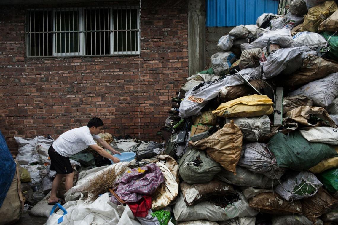 中國貴嶼鎮,2013年五月,一位貴嶼鎮居民正在電子廢料的袋之間收集雨水煮食。這個小鎮經過十年的「回收」工業,水已成為全中國最受污染的水源。