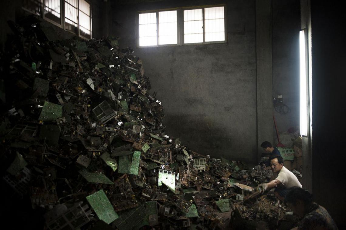 中國貴嶼鎮,2013年五月,三個工人在西方落伍的電子裝置前。
