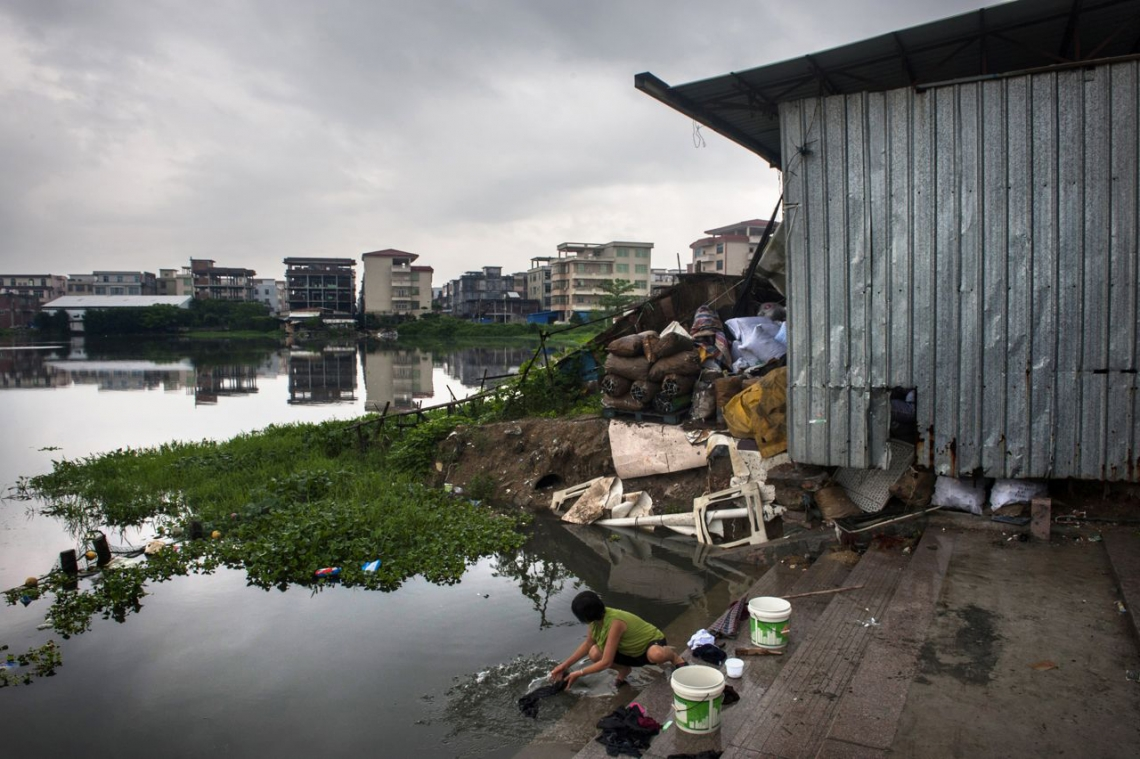 中國貴嶼鎮,2013年五月,一個女子正在貴嶼鎮河旁洗衣。