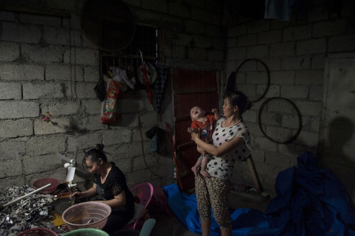 中國貴嶼鎮,2013年五月,正當工人在通風極差的工場燃燒塑膠零件,一個母親嘗試安撫她的兒子。