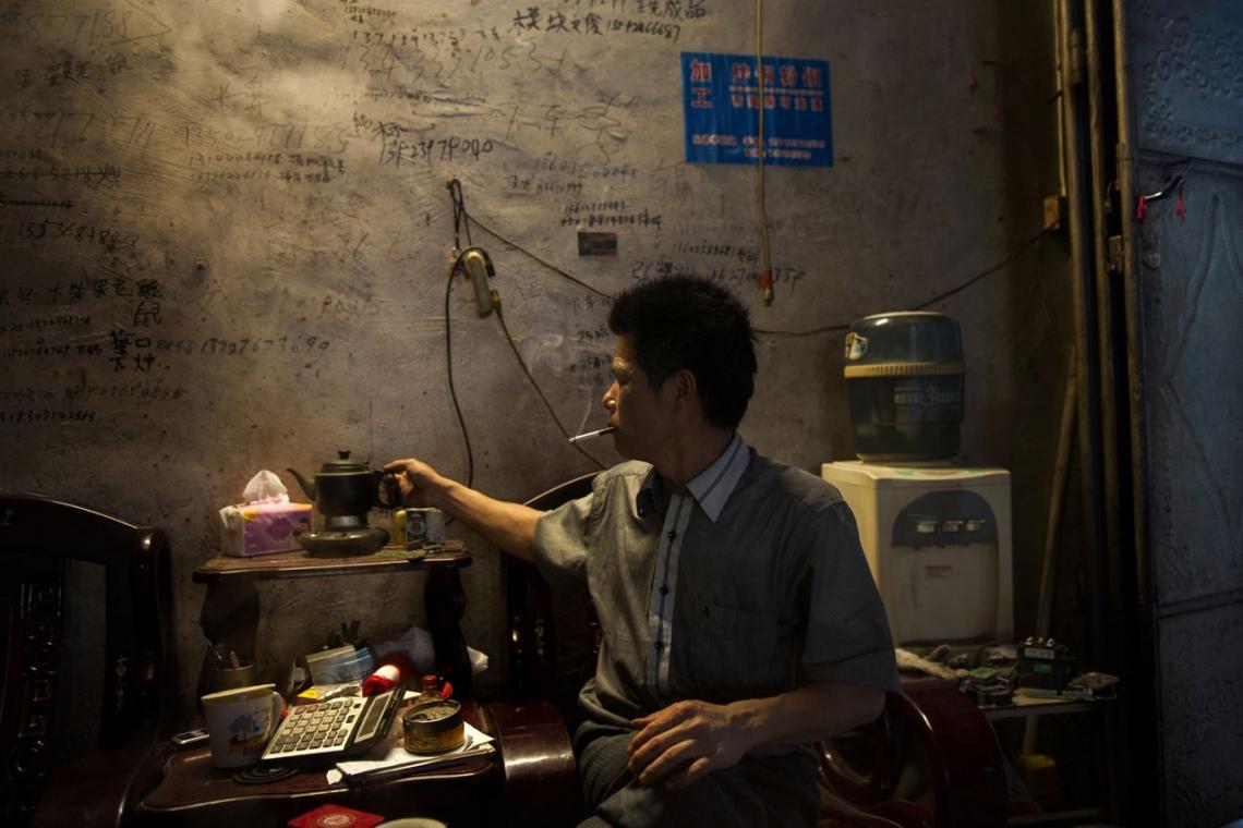 中國貴嶼鎮,2013年五月,非法工場的東主正為妻子泡茶。