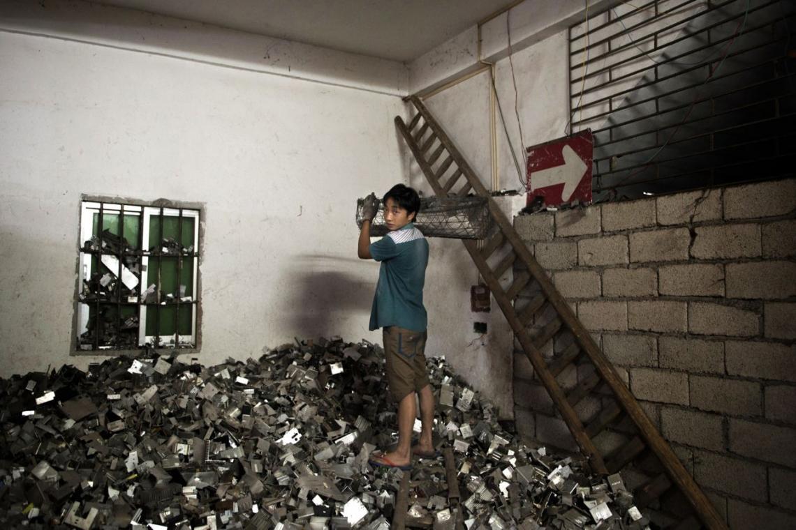 A boy loads electronic remains into a cart inside an illegal garage. Guiyu, China. May 2013.