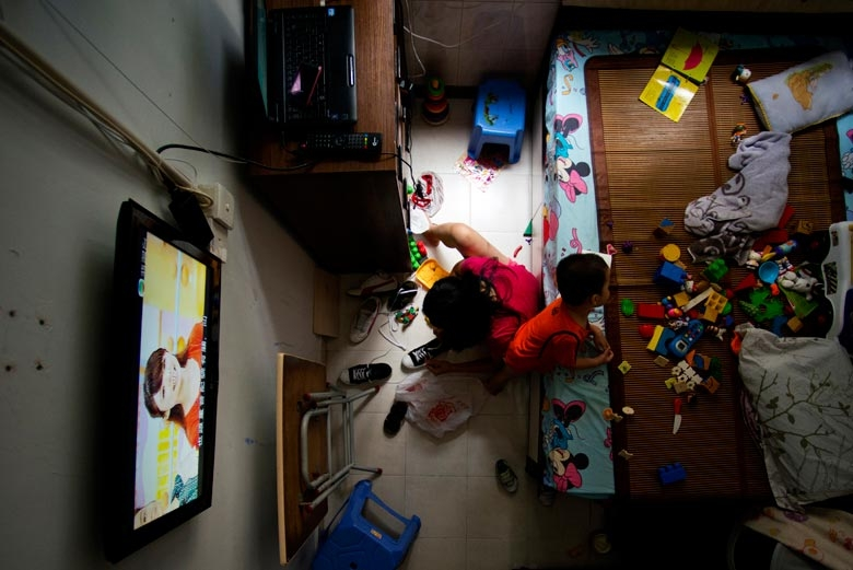 A family of three lives in a 100 sq. ft. subdivided flat in Tsuen Wan. The boy spends his days on his bed for both studying and playing, 2012.  From the series 'Cents' Mansion.