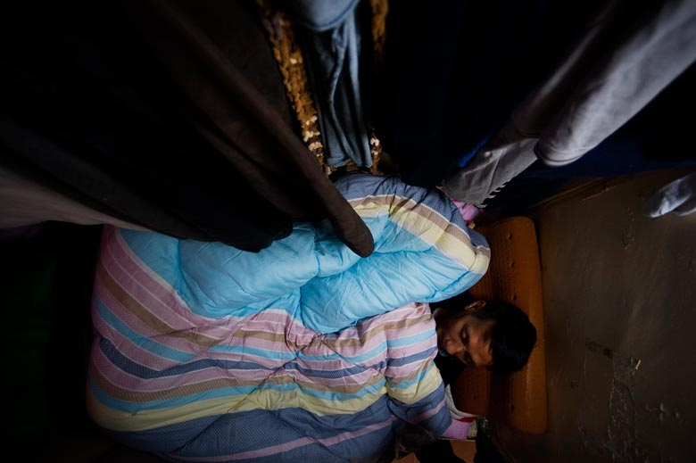 A single middle-aged man lives in a 'coffin room' (also know as a bed-space apartment) in Jordan. There are a total of 30 'coffins' in a single flat with upper and lower levels. The rent for a 'coffin' is over HK$1,000, 2011.  From the series 'Cents' Mansion.