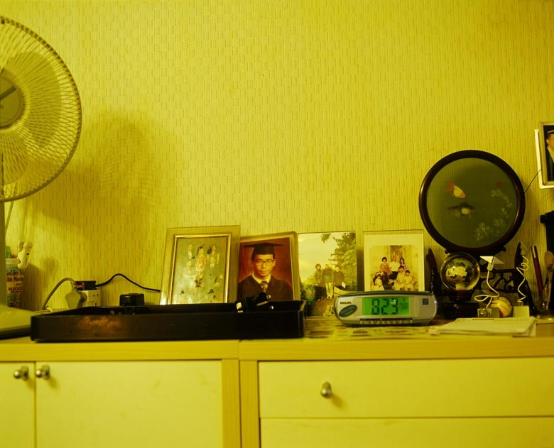 Mr Au's son's graduation photo sits alongside other family photos in the family's living room, North Point.